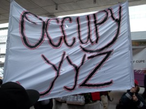 Banner carried by wildcatting workers at Pearson International Airport, March 22/23 2012