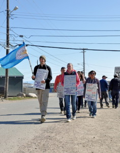 About two dozen unionized QEC workers walk the picket line near Iqaluit's QEC office July 23. The strike entered its eighth day July 23, with no indication from either side that negotiations would resume any time soon. Photo by Thomas Rohner