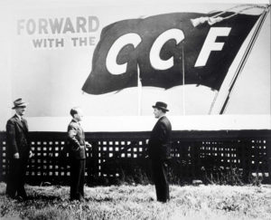 Tommy Douglas (centre) standing under a CCF billboard after the 1944 election victory.
